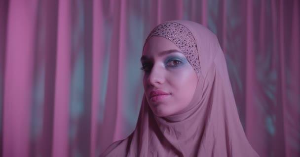 Caucasian girl hijab neon make-up portrait light night purple violet white background