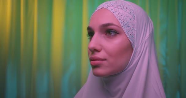Caucasian girl white hijab neon make-up portrait light night background