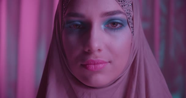 Caucasian young girl in hijab neon purple color background portrait makeup rotates in camera look shadow night eyes makeup