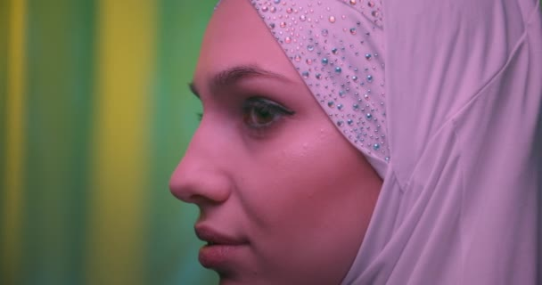 Close-up Beautiful confident girl in white hijab neon green background glitter view profile make-up