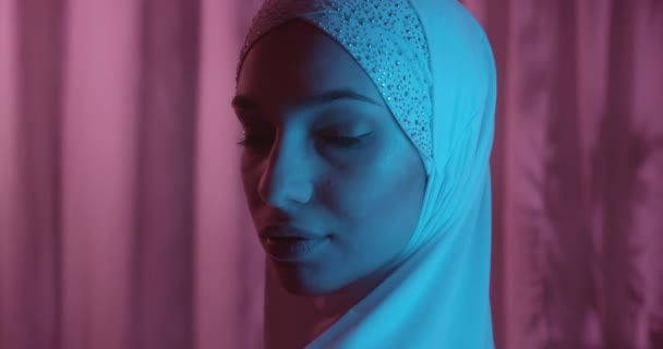 Beautiful portrait Caucasian confident portrait girl in white hijab neon magenta background glitter make-up blue light ray shadow silhouette evening profile