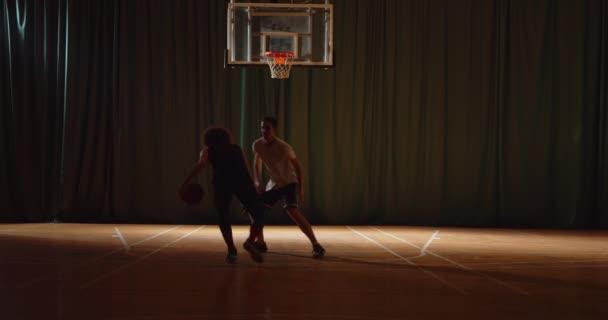 Összességében két fiatal kosárlabda játékos kosárlabda verseny amatőrök terem sport parketta sziluettek csöpögő ellenzék védelmi blokk éjszakai játék