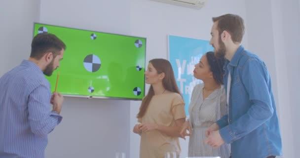 Nettes junges kaukasisches Mädchen zeigt eine Präsentation für ihre Kollegen Bürogeschäft Multirace kollektive Freunde kreatives Lachen Witz