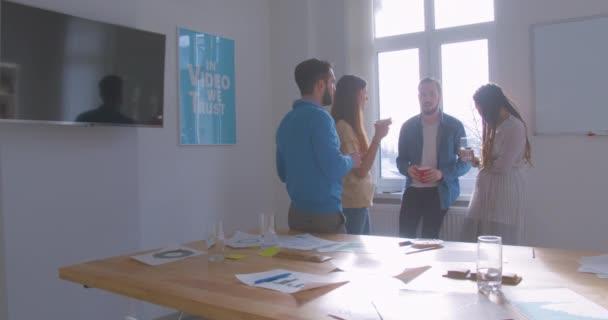 Čtyři různé multi-rasové kolegové v kanceláři přestávka konverzace rozhovor smartphone diskuse slunný pokoj zbytek