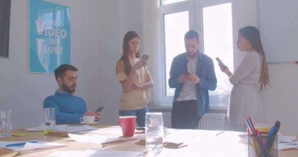 Vier multiethnische Kollegen in der Kaffeepause im Büro nutzen Smartphone und Internet
