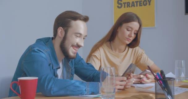 Junge Kollegen im sonnigen Büro nutzen Smartphones und lächeln