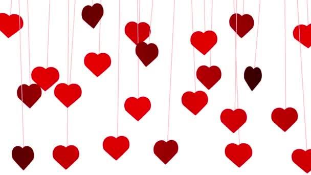 Animované červené srdce tvary visící z nití na bílém pozadí