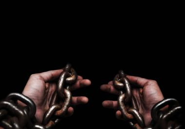 Victim, Slave, Prisoner male hands tied by big metal chain