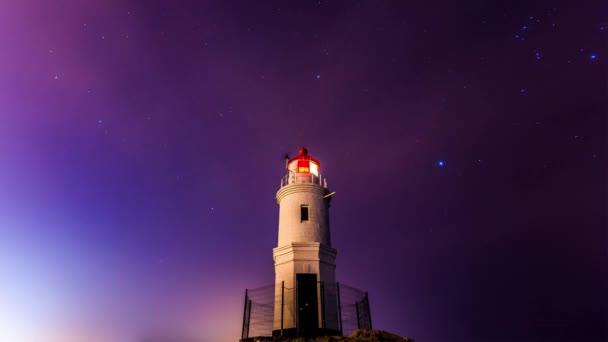 Leuchtturm-Zeitraffer in der Nacht mit Sternen und Wolken. tokarevsky Leuchtturm, Wladiwostok, Russland. Es ist ein Aussichtspunkt, der zeigt, wo das Land aufhört und der Pazifik beginnt