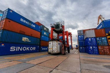 Summer, 2015 - Vladivostok, Russia - Vladivostok Sea Container Terminal. A loader loaded with a container moves along the territory of a trading port against the background of containers