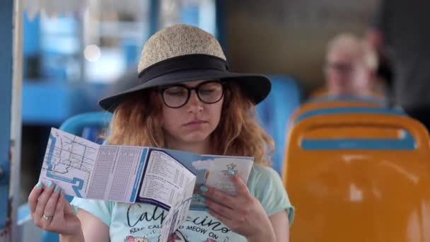 Turistický výlet lodí na řece Chao Phraya v Bangkoku. Krásná dívka evropského vzhledu s brýlemi a kloboukem sedí v turistické lodi a studuje průvodce Thajskem.