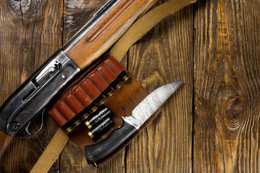 Hunting rifle and ammunition lie on wooden background. Copy space