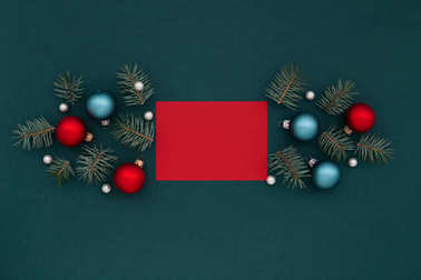 Red card and Christmas decoration on shaded spruce background