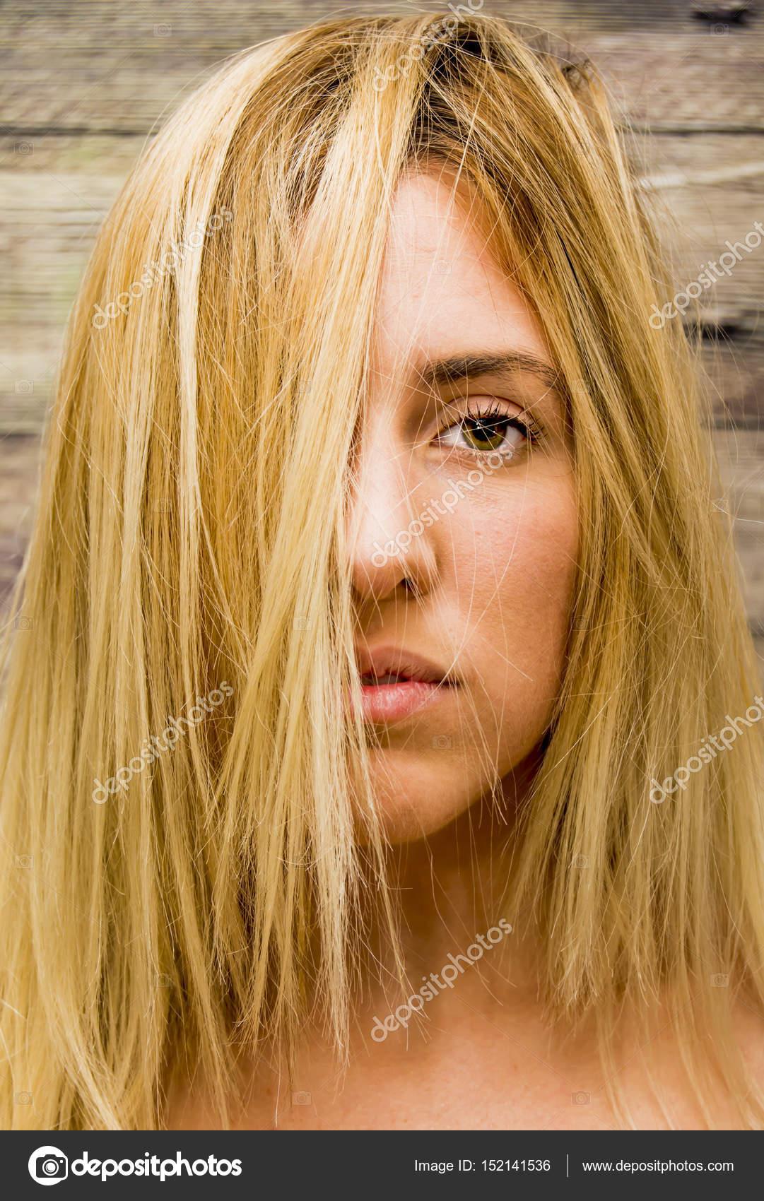 Bella donna bionda con i capelli che cadono sul suo fronte sopra fondo di  legno — Foto di ... a382a4d765b3