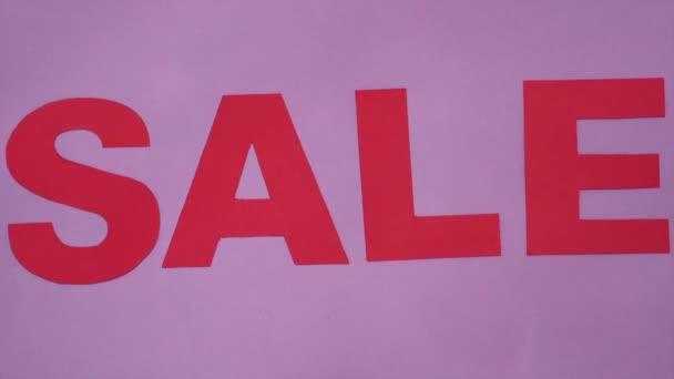Draufsicht auf farbige, helle Verkaufsbeschriftung. rote Buchstaben aus Papppapier auf lila Papier Hintergrund geschnitten.