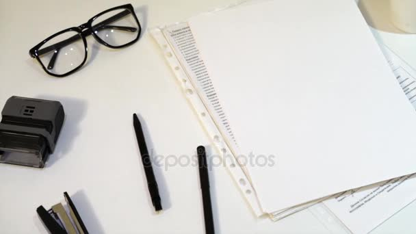 papíru, pera, sešívačku a brýle na bílém stole