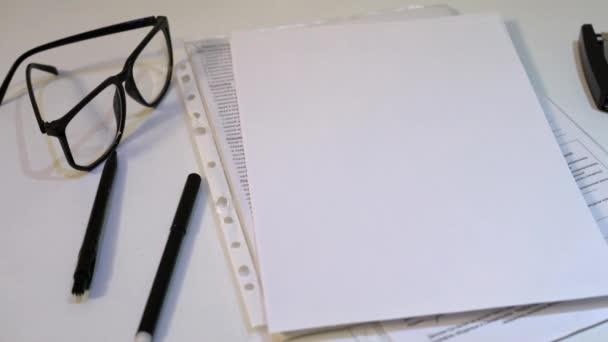 Kancelářský bílý stůl. papíru, pera, sešívačku a brýle na bílém pozadí
