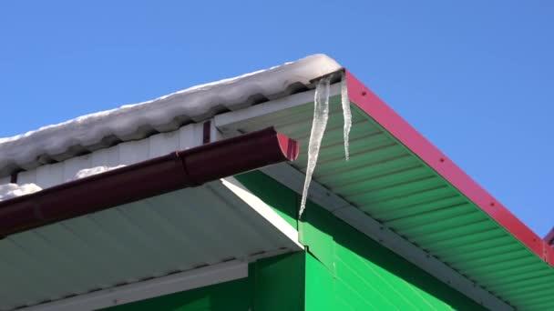 voda kape z rampouchy na střeše domu zblízka