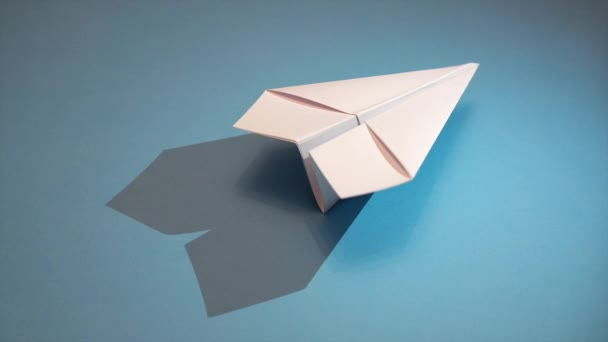 white paper plane on a blue paper background. The moving shadow under the airplane creates the illusion of flying