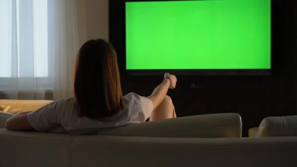 Dívka sleduje televizi se zelenou obrazovkou, zatímco sedí na pohovce a drží cestu v ruce.