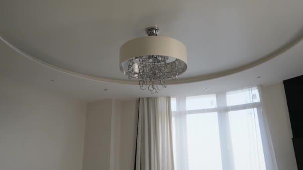 V rohu interiéru světlého obývacího pokoje. Strop, kožená pohovka a květináč.