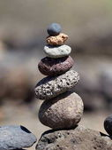 stack of black volcanic stones on the beach