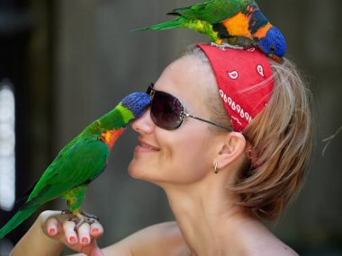 woman with funny parrot on her head