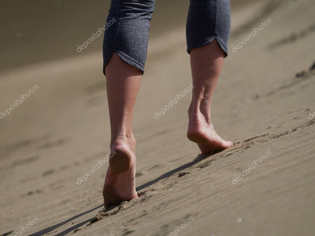 woman jogging/walking on the beach at sunrise