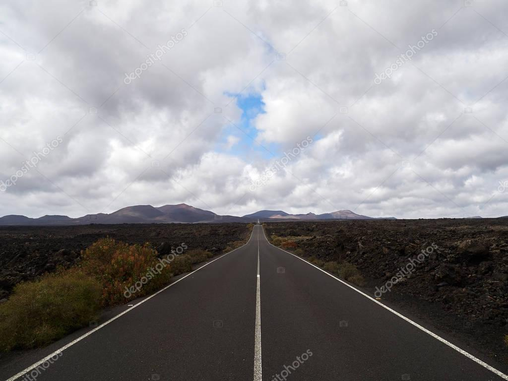 Empty endless highway through the volcanic landscape