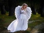 Fényképek fiatal nő, fárasztó, hosszú, fehér ruhát, és angel szárnyak