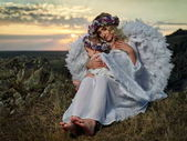 Young beautiful mother hugging her little daughter outdoor in summer sunset light, angels