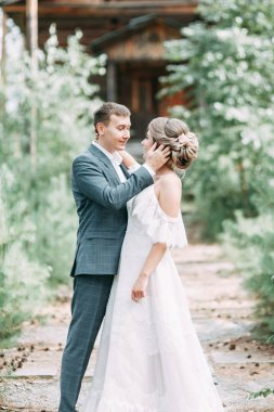 Stylish couple on the background of a wooden temple. Wedding in nature in the woods.