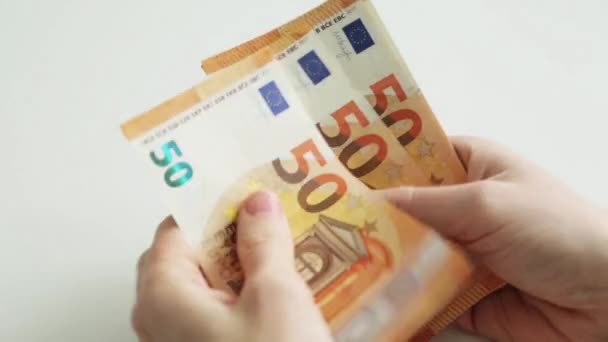 Euro paper money account. 50 Euro banknotes. Lay out the money on a white background. A mans hands count.