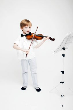 Little cute red-haired boy with a violin in his hands