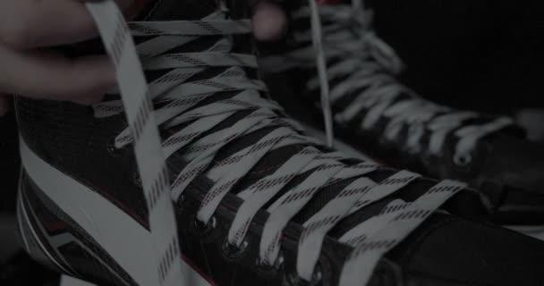 Hráč v hokeji, váže tkaničky na bruslích, na černém pozadí