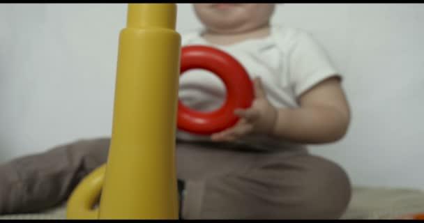 Malé dítě (chlapec), leží hrací hračka pyramida, bílé pozadí. Koncepce: děti, veletrh kůže, krásné děti