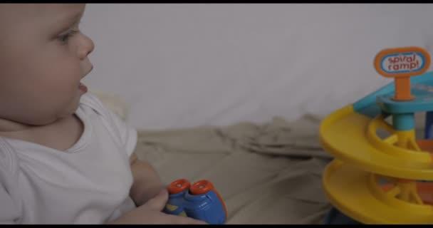 Portrét krásné malé batole (boy), se nachází hrací hračky auta, blond, světlé vlasy, modré oči, bílé pozadí. Koncepce: děti, veletrh kůže, krásné děti