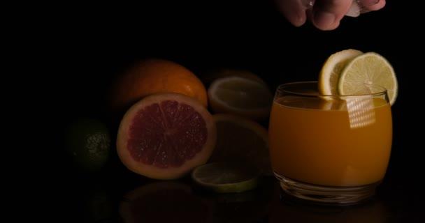 Pomerančová šťáva ve sklenici, citrusové plody, černé pozadí