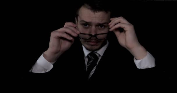 Portrét pohledný mladý podnikatel v brýlích, oblek, černé pozadí.