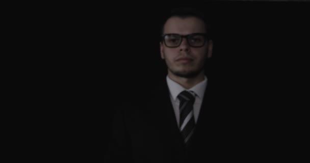 Pohledný mladý podnikatel nošení brýlí, ukazuje palec nahoru (jako), v obleku, černé pozadí.