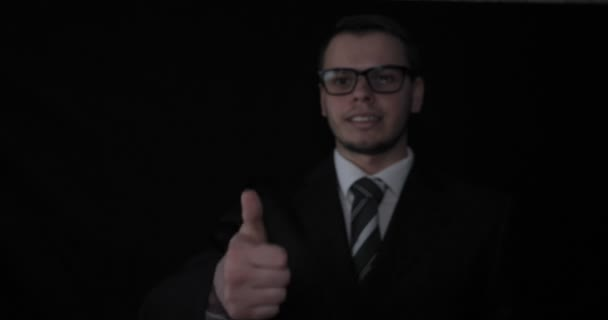 Handsome young businessman wearing glasses, showing thumbs up (like), in suit, black background.