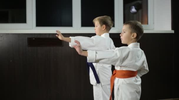 A fiúk gyakorolják a rúgásokat a karate állványokban.