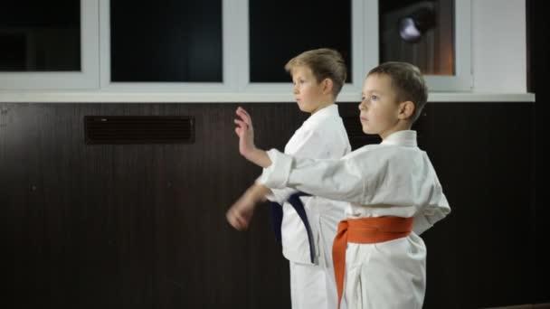 A gyerekek gyakorolják a szopást a karate állványon.