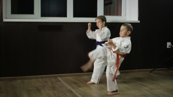 Chlapci sportovci trénují kopance do nohou
