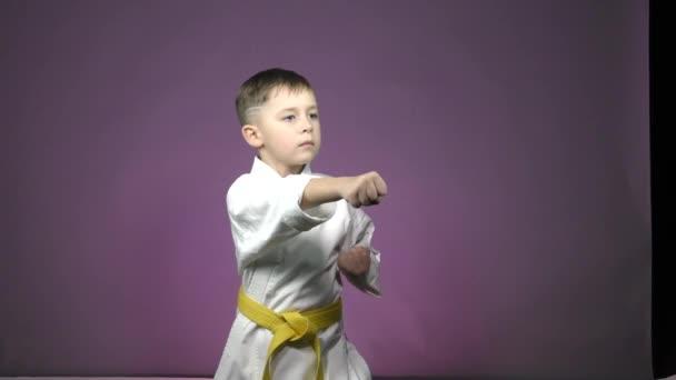 Kis sportoló edz ütések karate álláspont lila háttér