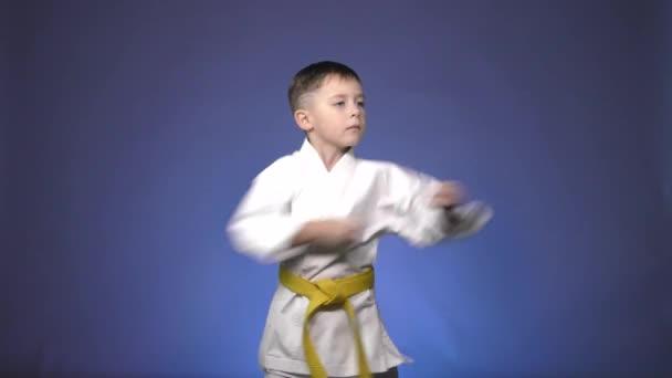 Kis sportoló végez ütések karok kék alapon