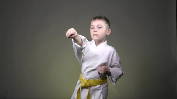 Kis sportoló végez ütések karok sötét szürke háttér