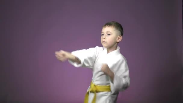 A lila háttér, egy kis sportoló végez ütések karok