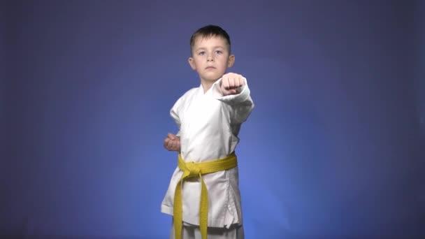 Aktív kis sportoló veri ütések karok kék alapon