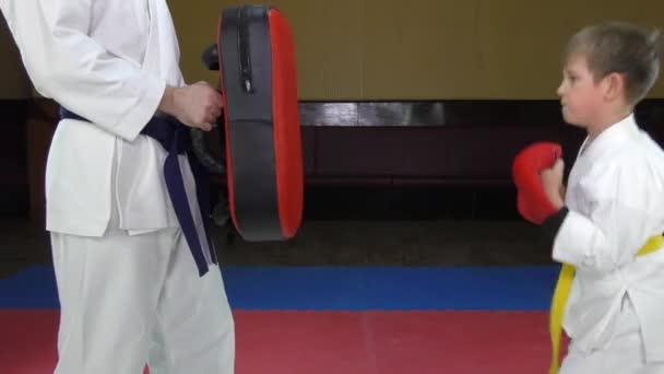 A sportoló üti a piros tornatermi felszerelést az edző kezében.